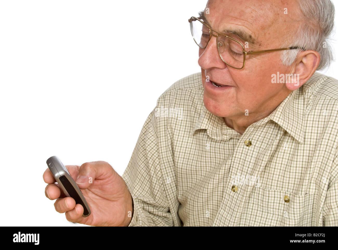 Vertical horizontal de un anciano caballero tiene dificultades para usar los botones pequeños en un teléfono móvil Foto de stock