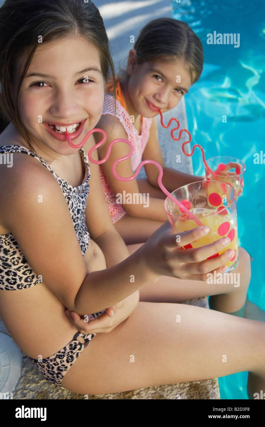 5bfa961d Las niñas beber jugo de crazy pajas en el borde de la piscina, Retrato