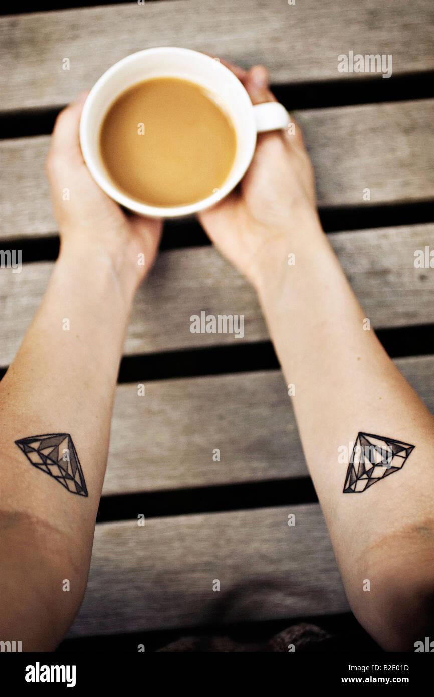 Cerca de la mano de una mujer sosteniendo una taza de café Imagen De Stock