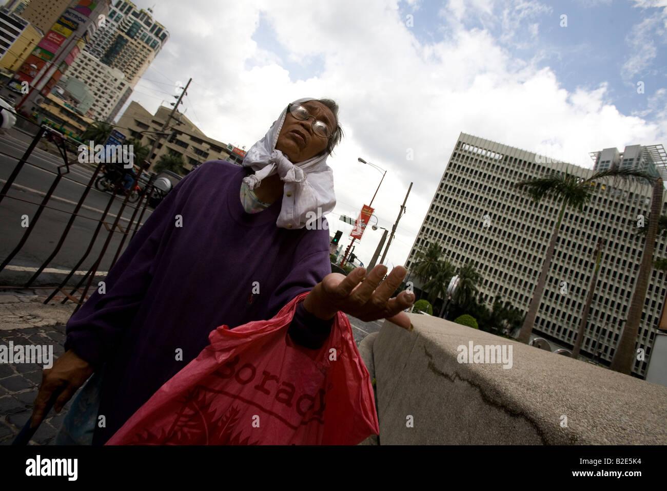 Una anciana suplica por dinero en Makati City, Manila, Filipinas. Imagen De Stock