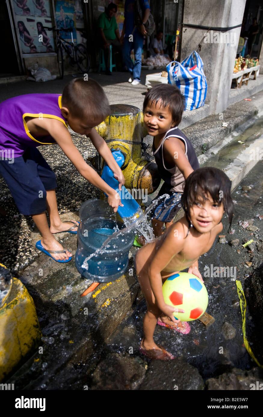 Los niños filipinos se bañan en la calle, cerca del distrito de la ciudad de China en Manila, Filipinas. Imagen De Stock