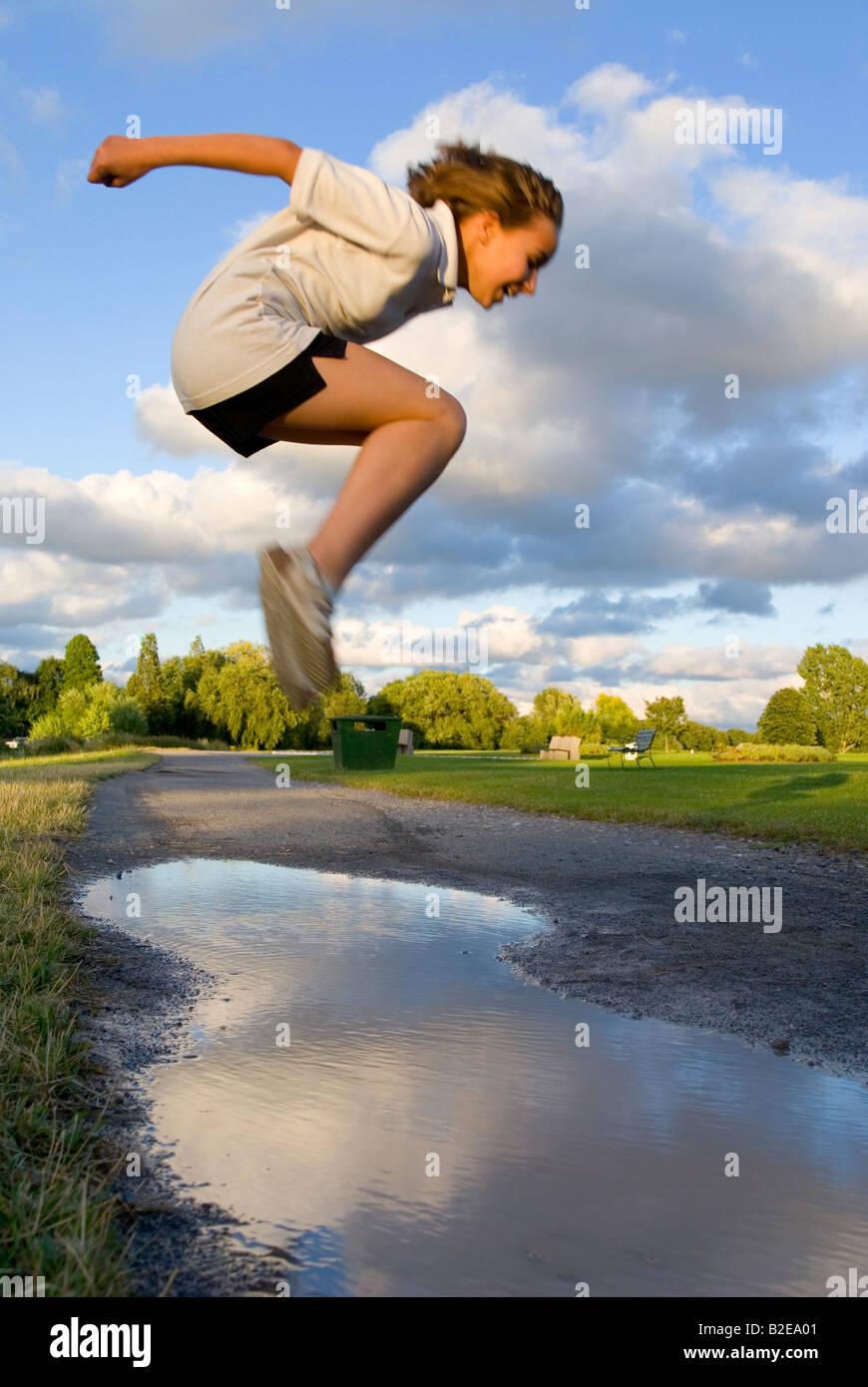 El perfil lateral de la niña saltando en el aire. Imagen De Stock