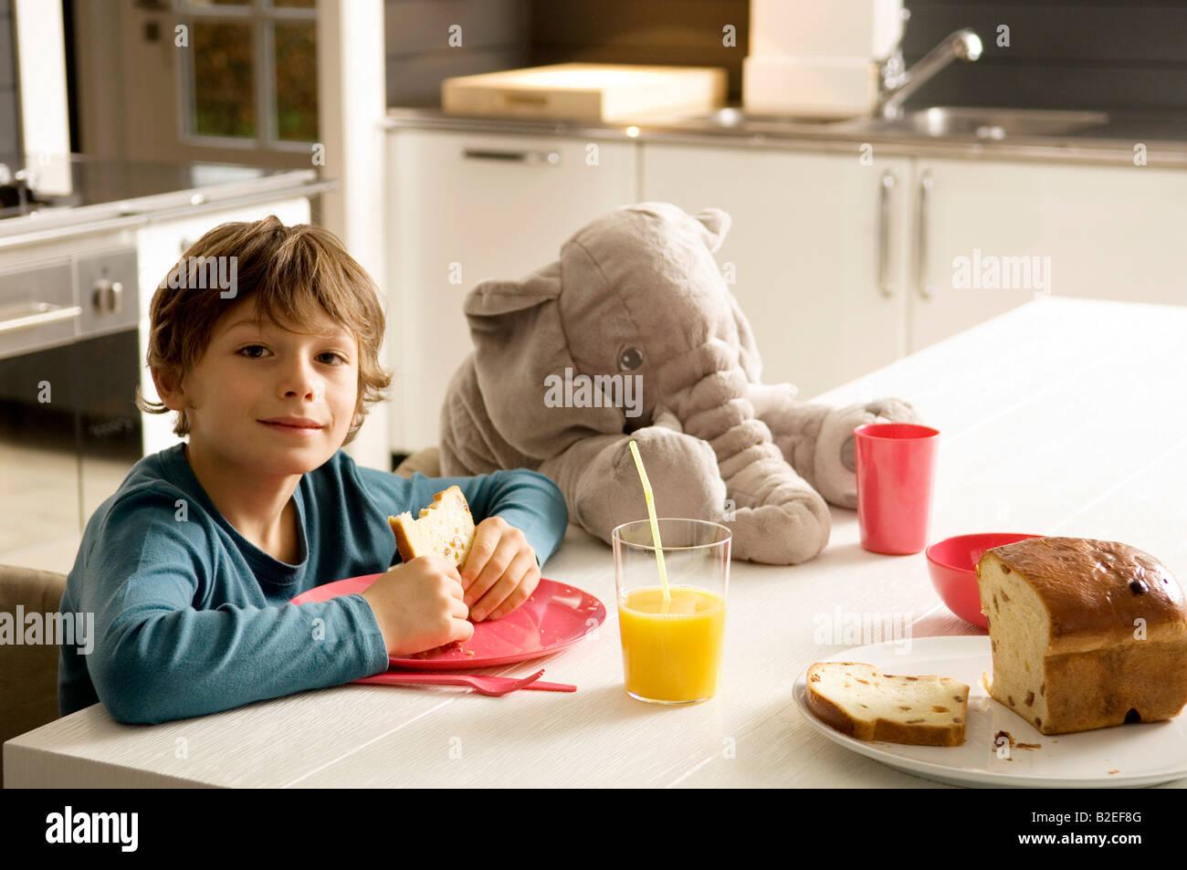 Retrato De Un Niño Tomando El Desayuno En La Cocina Foto
