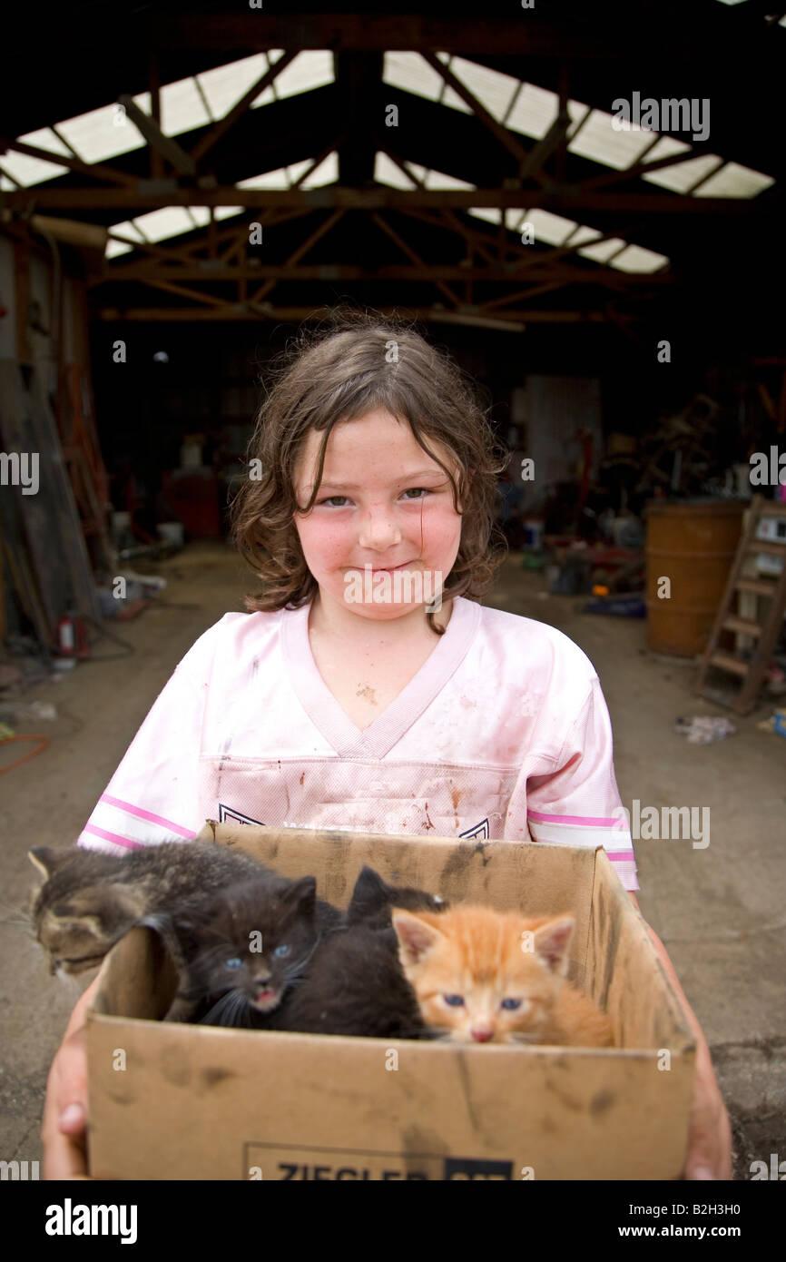 Joven en la zona rural de Iowa, sosteniendo la caja de nuevo los gatitos, Iowa, EE.UU. Foto de stock
