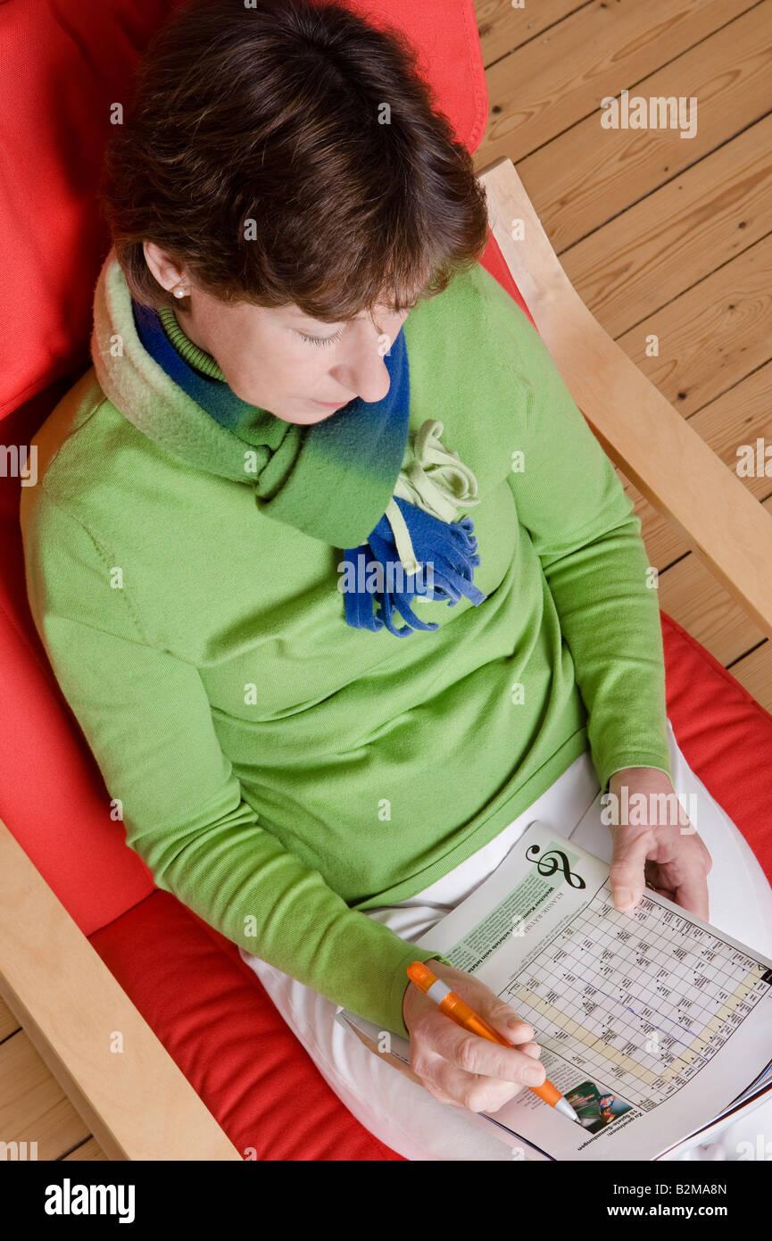 Mujer de mediana edad haciendo un crucigrama Imagen De Stock
