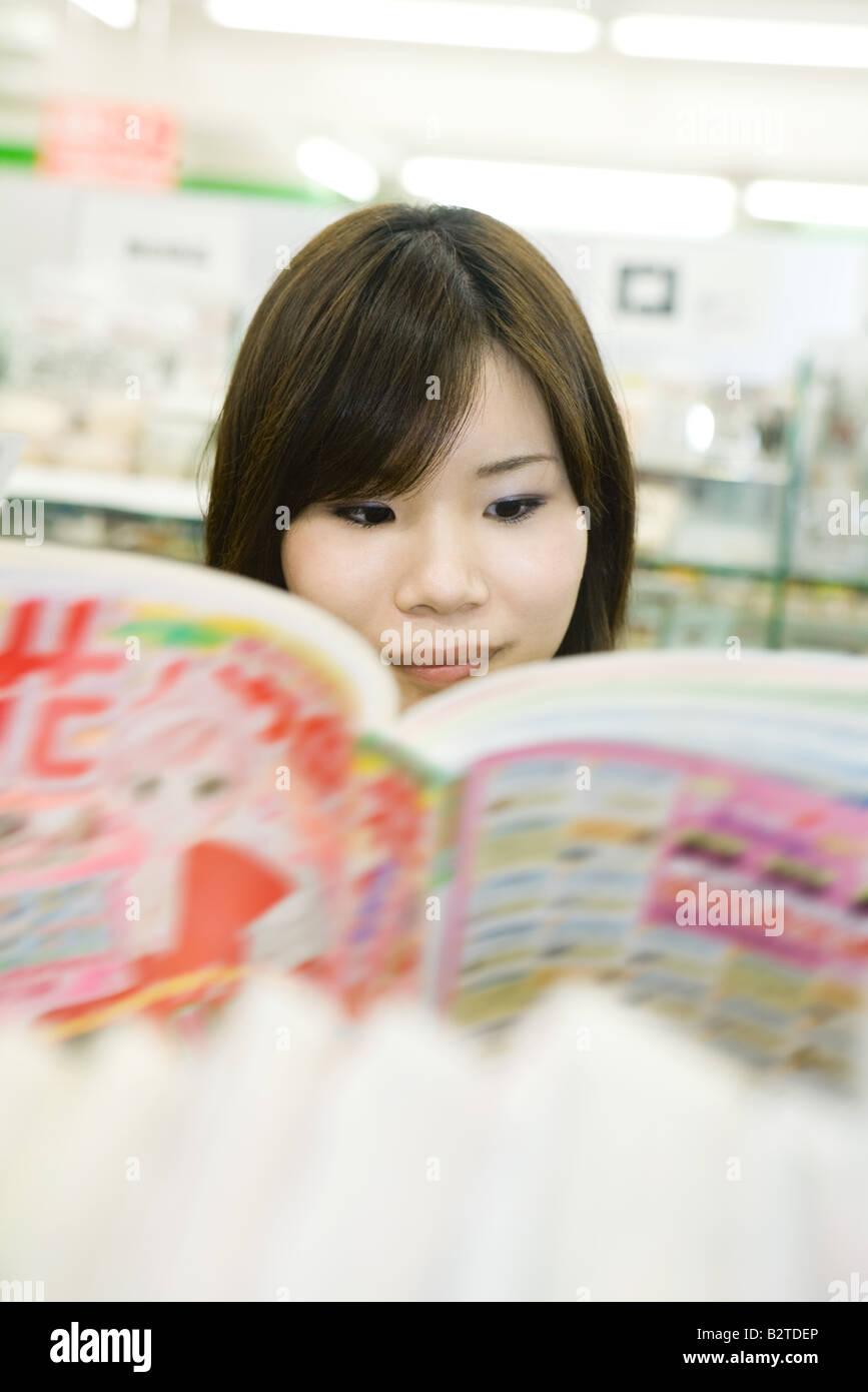 Jovencita japonesa leyendo cómics, el enfoque selectivo Imagen De Stock