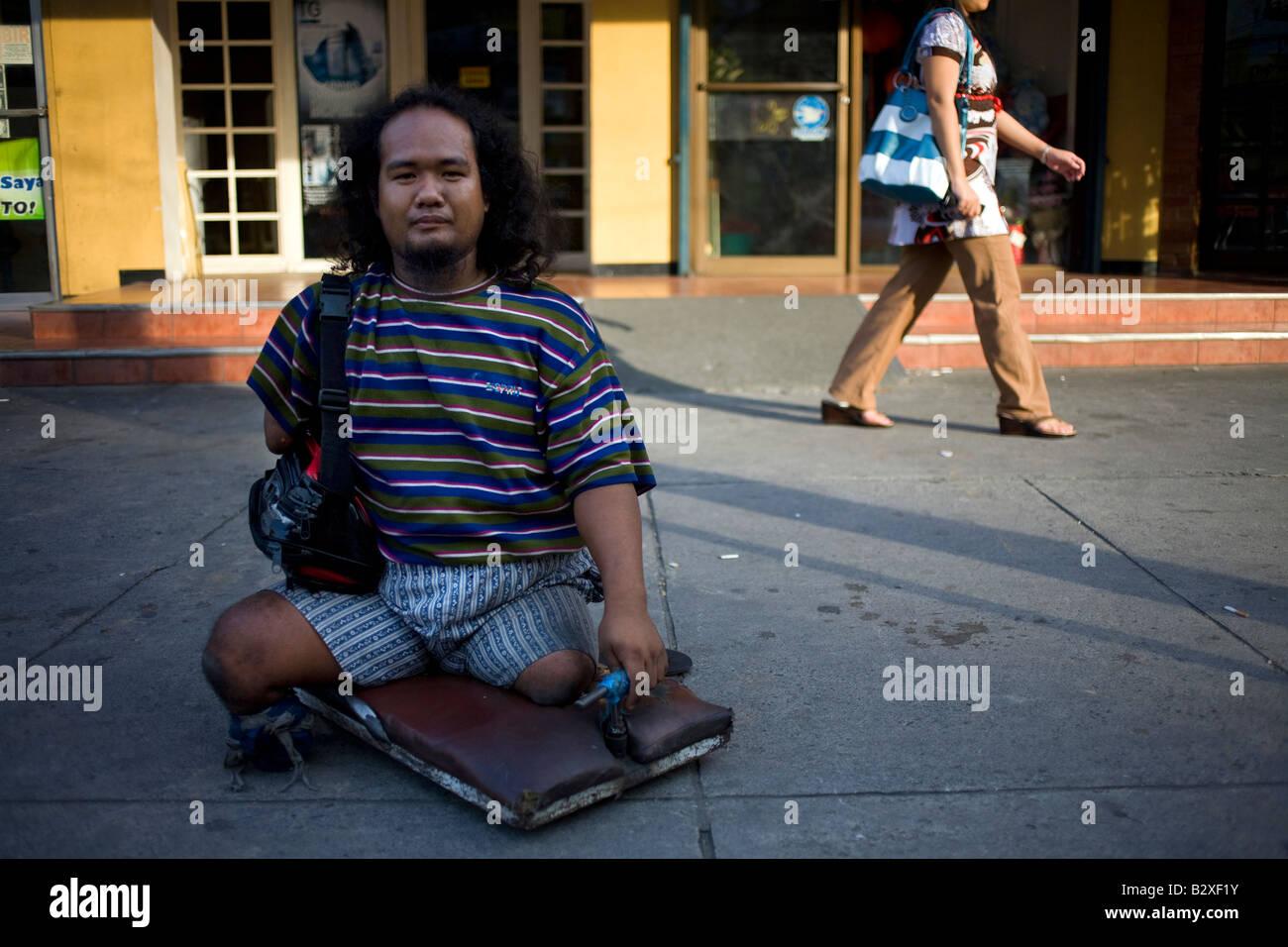 Un Filipino físicamente incapacitados suplica por dinero en la calle en Makati City, Manila, Filipinas. Imagen De Stock