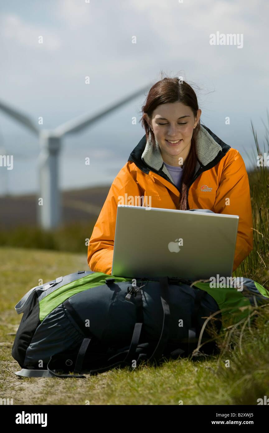 Mujer con portátil y turbina eólica en segundo plano. Foto de stock