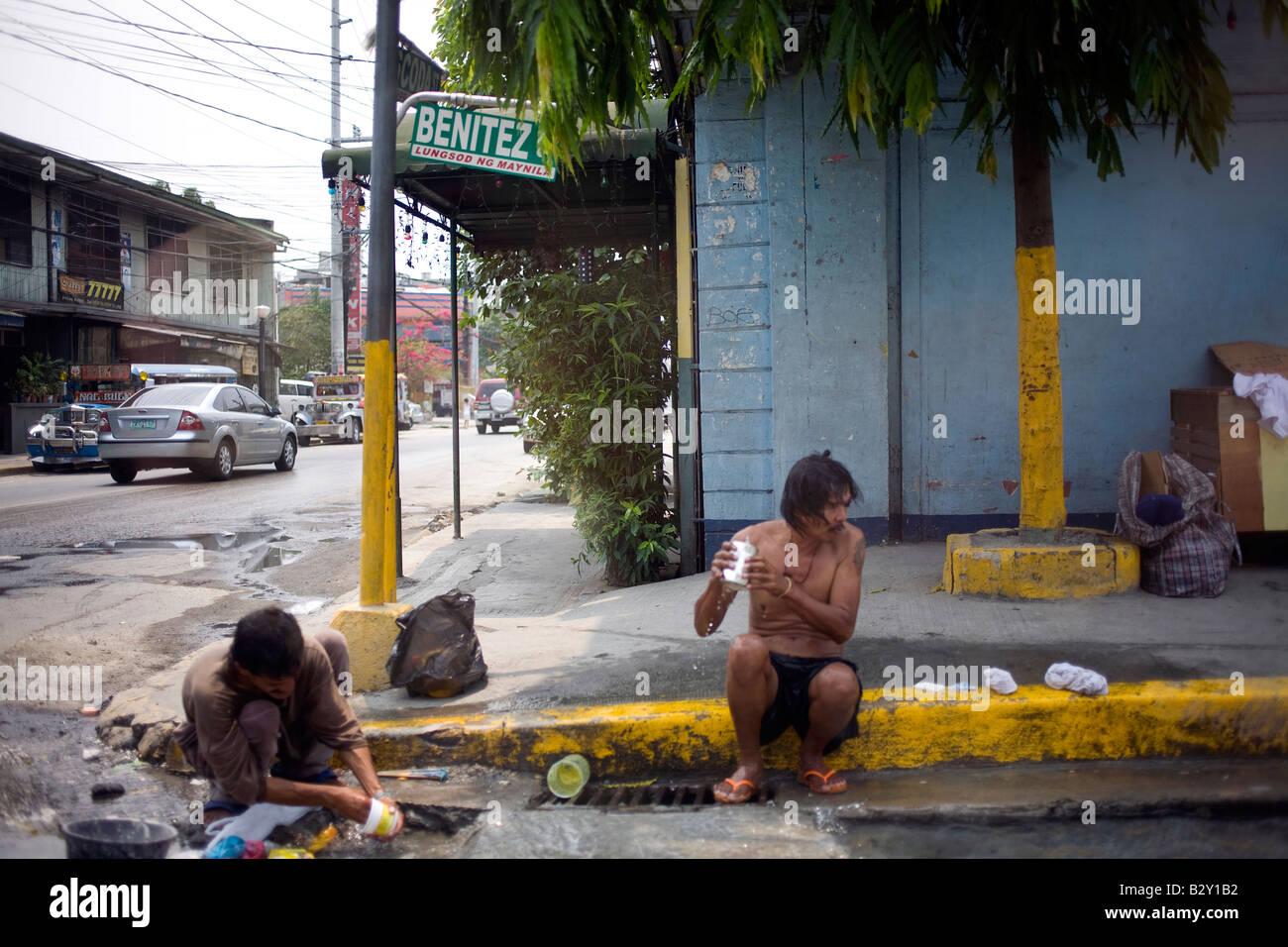 Dos pobres Filipinos bañarse con agua en una alcantarilla en Manila, Filipinas. Imagen De Stock