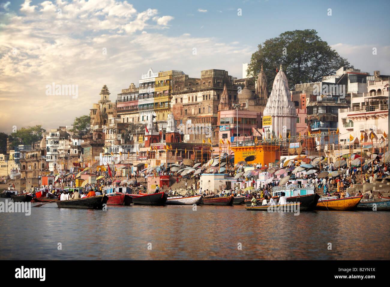 El río Ganges en primer plano con los barcos, los templos y cielo azul de Varanasi, en India en el fondo. Imagen De Stock