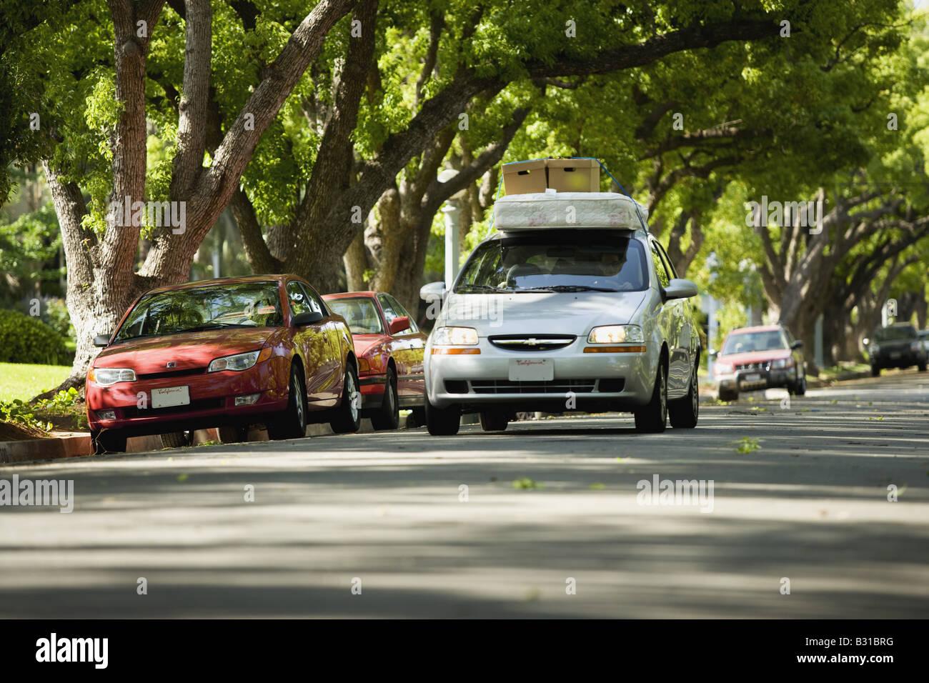 Chevy Aveo bajando la calle arbolada con colchón y cajas en el techo Foto de stock