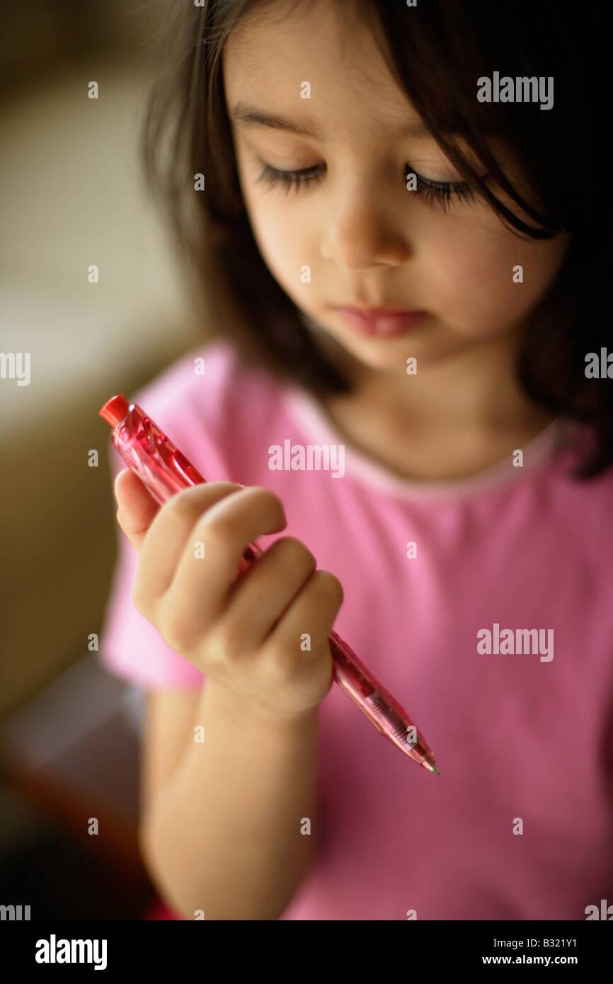 Considerando un bolígrafo de cinco años de edad, niña mira una pluma roja Imagen De Stock