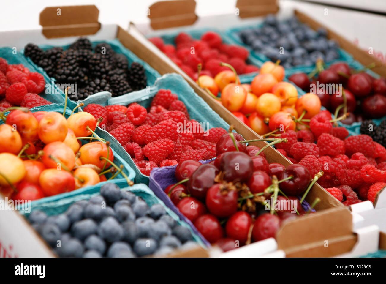 Caja de frambuesas y cerezas en la pantalla en el mercado Imagen De Stock