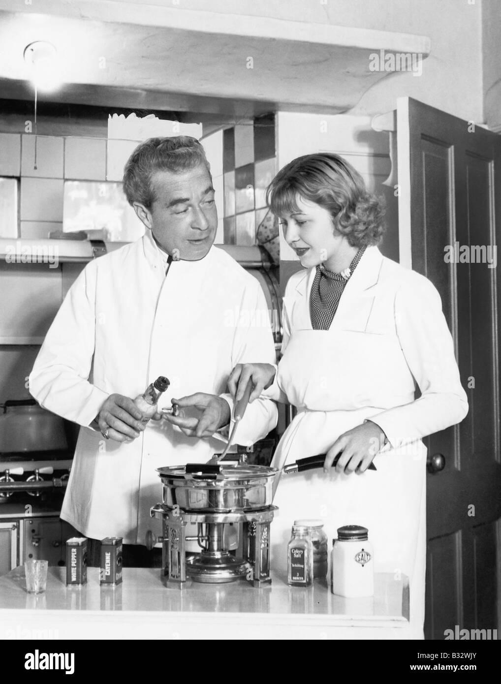 La pareja en la cocina preparando una fondue Imagen De Stock