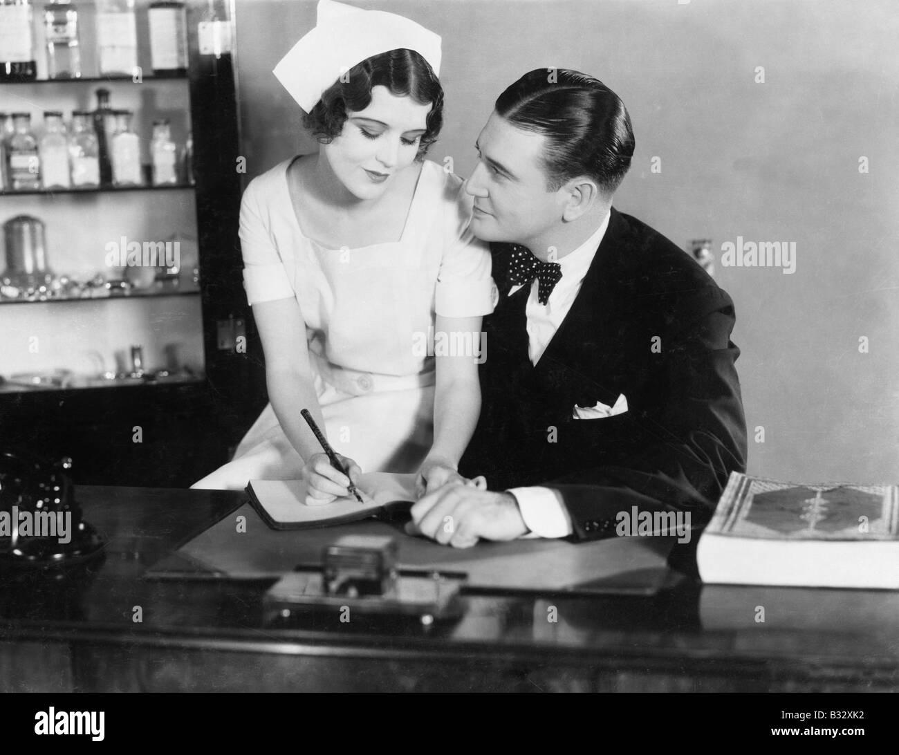 Enfermera sentada en el regazo del médico Foto de stock