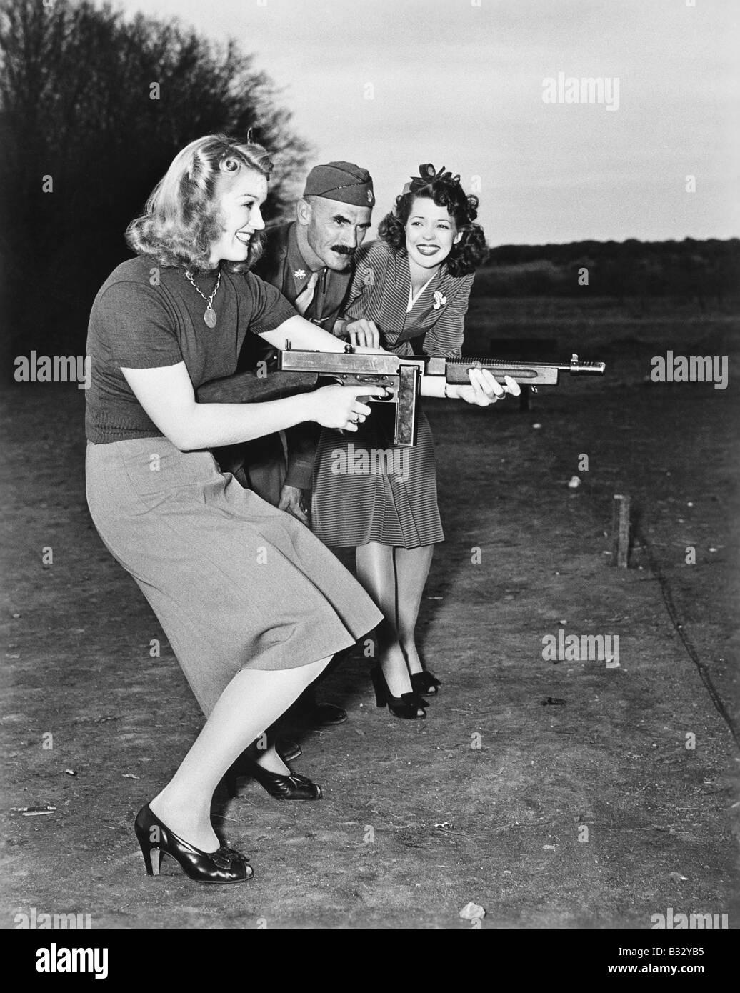 Dos jóvenes mujeres y un soldado probando una ametralladora Imagen De Stock