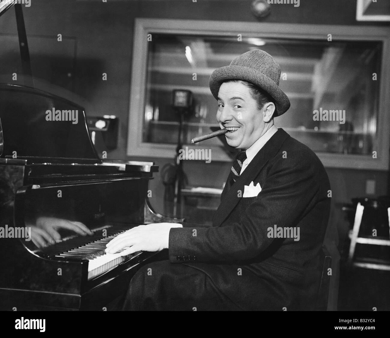 Hombre con una gran sonrisa y un cigarro en la boca tocando el piano Imagen De Stock