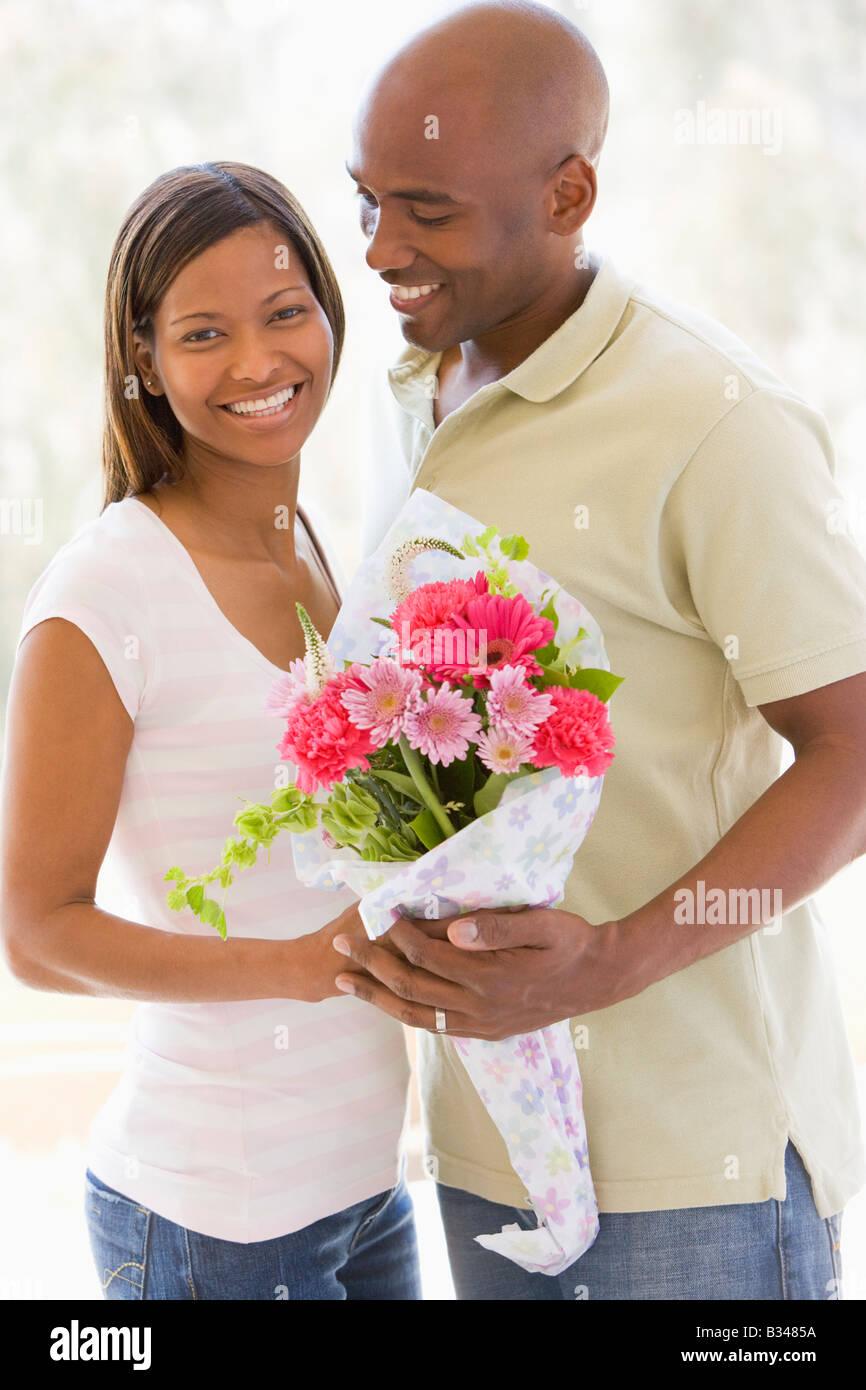 El marido y la mujer sosteniendo flores y sonriente Imagen De Stock