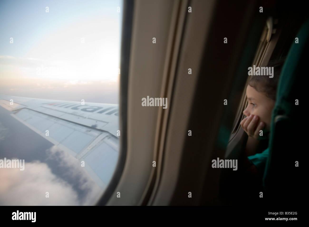Niña mirando fuera de la ventana de un vuelo de Airbus Foto de stock