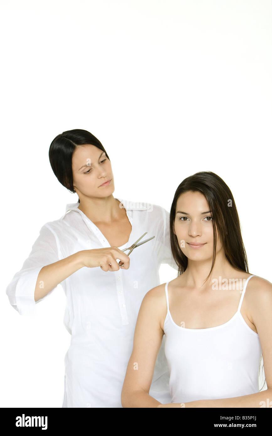 Mujer consiguiendo su cabello cortado por el estilista, sonriendo a la cámara Imagen De Stock