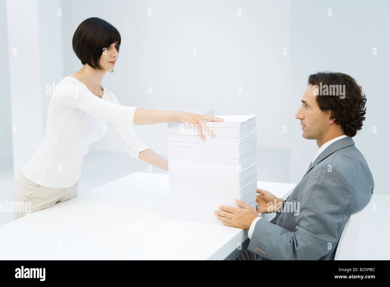 Mujer profesional y empresario intercambiar tall pila de papel a través de escritorio Imagen De Stock
