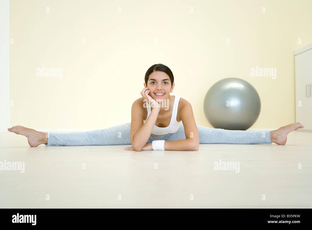 Mujer joven hacer split en el suelo, sonriendo a la cámara Imagen De Stock