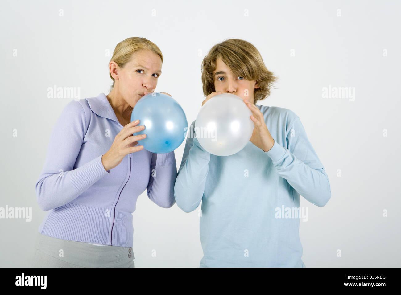 La madre y el hijo adolescente de pie al lado de la otra, inflando globos, mirando a la cámara Imagen De Stock