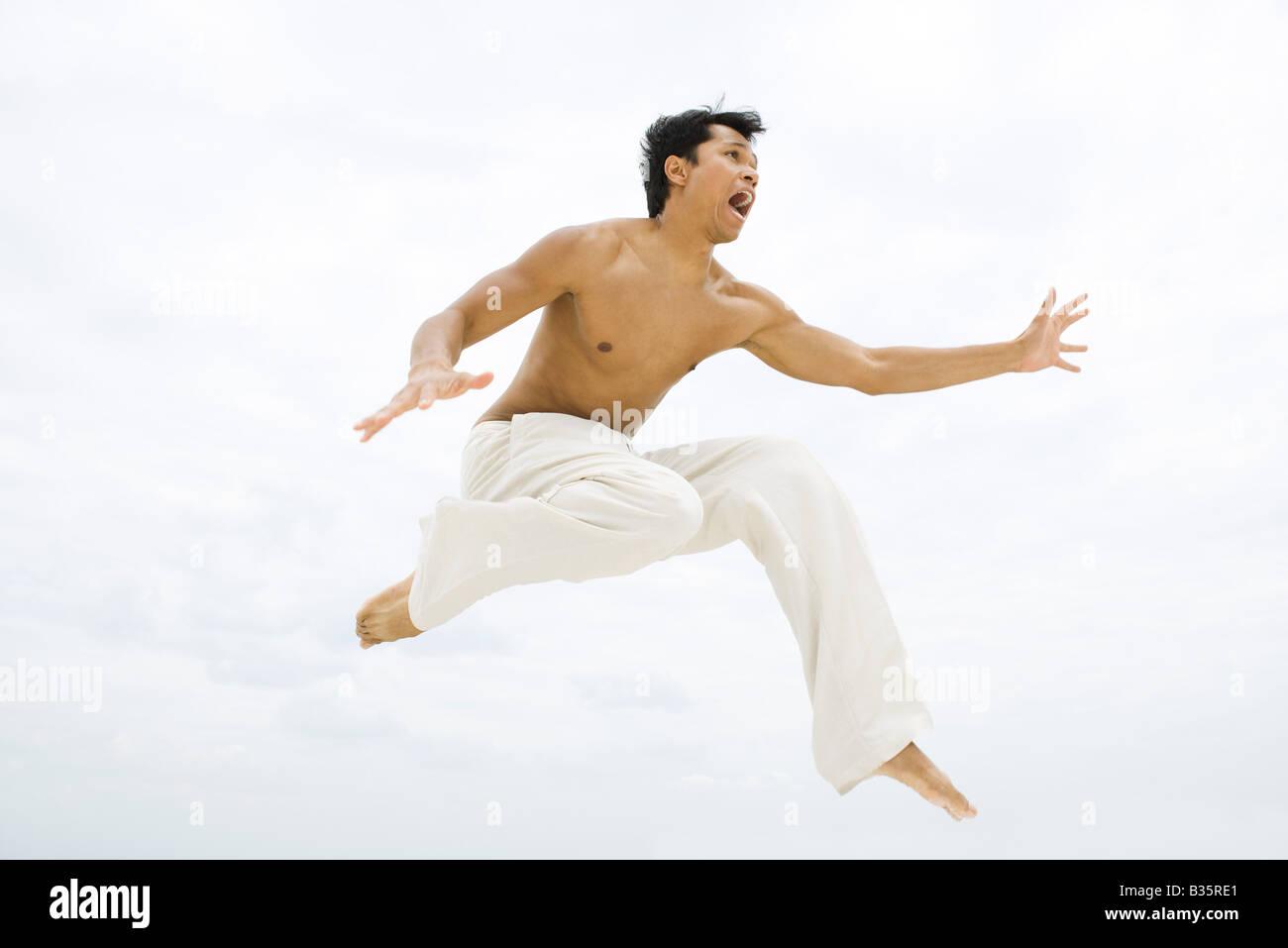 Hombre saltando en el aire, vista lateral Imagen De Stock