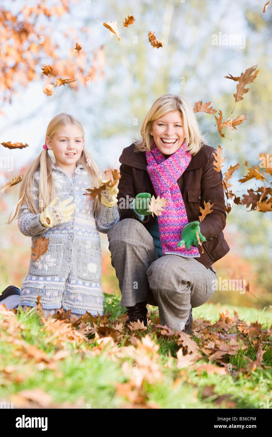 Mujer y joven al aire libre en el parque jugando en hojas y sonriendo (enfoque selectivo) Foto de stock