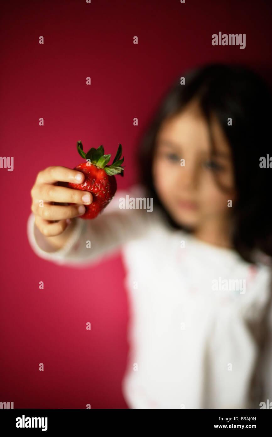 Cinco años de edad, niña sostiene fresa Imagen De Stock