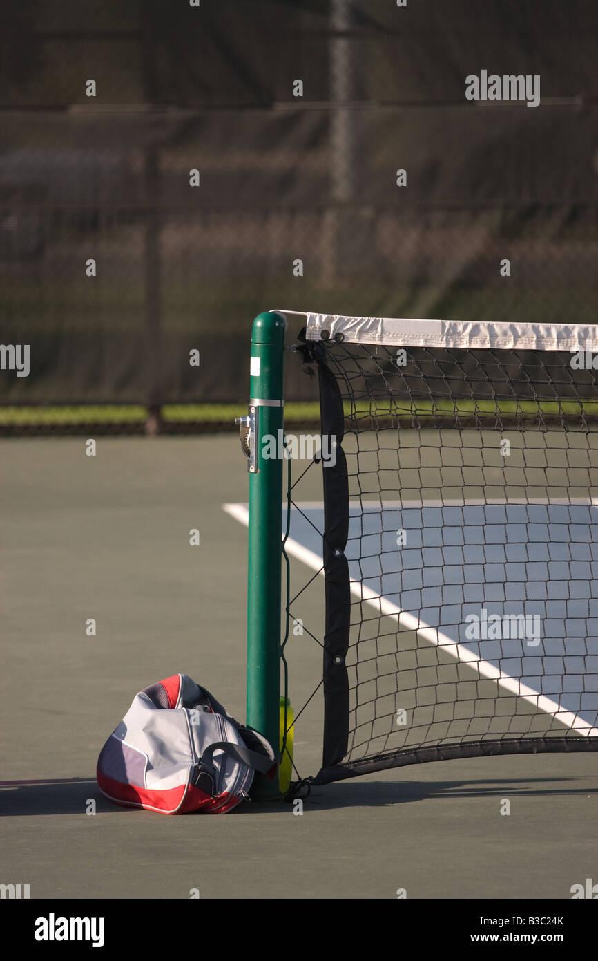 Bolsón sentado en la pista de tenis con la esquina de la corte y parte de la red que muestra Imagen De Stock