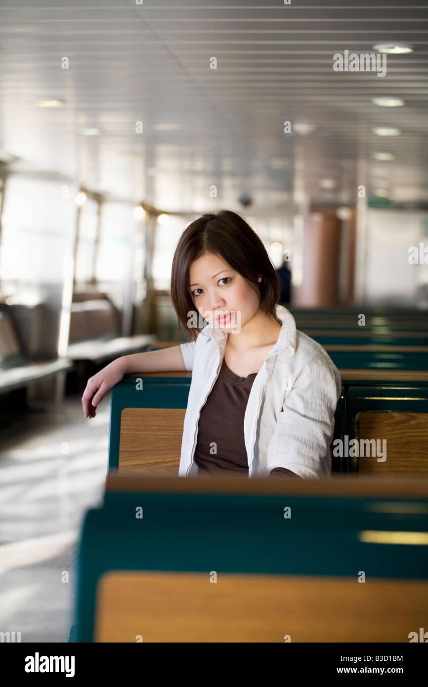Mujer joven sentado en un banco y miraba Foto de stock