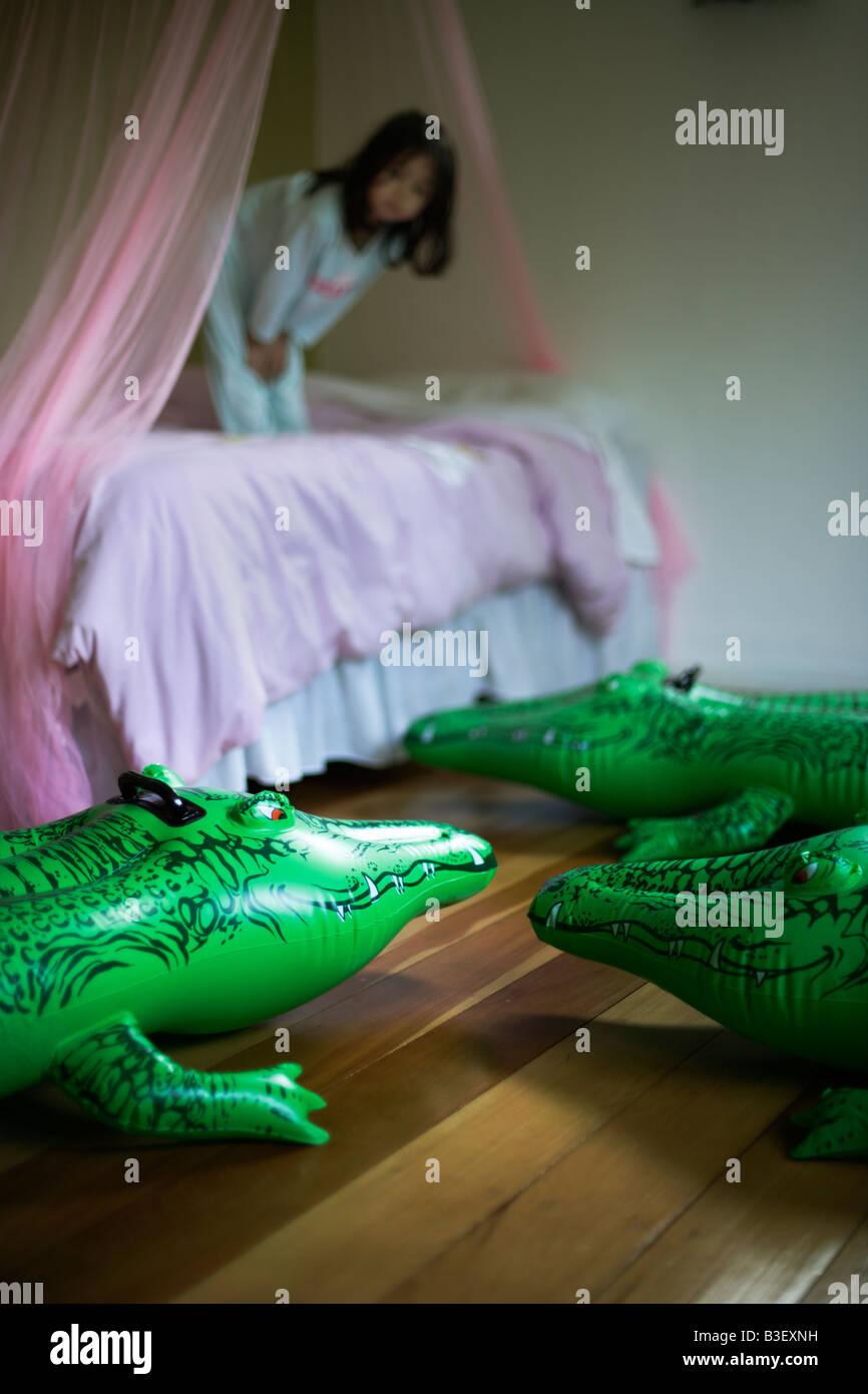 Serie de cocodrilo inflable que acechan por una cama de niño Imagen De Stock