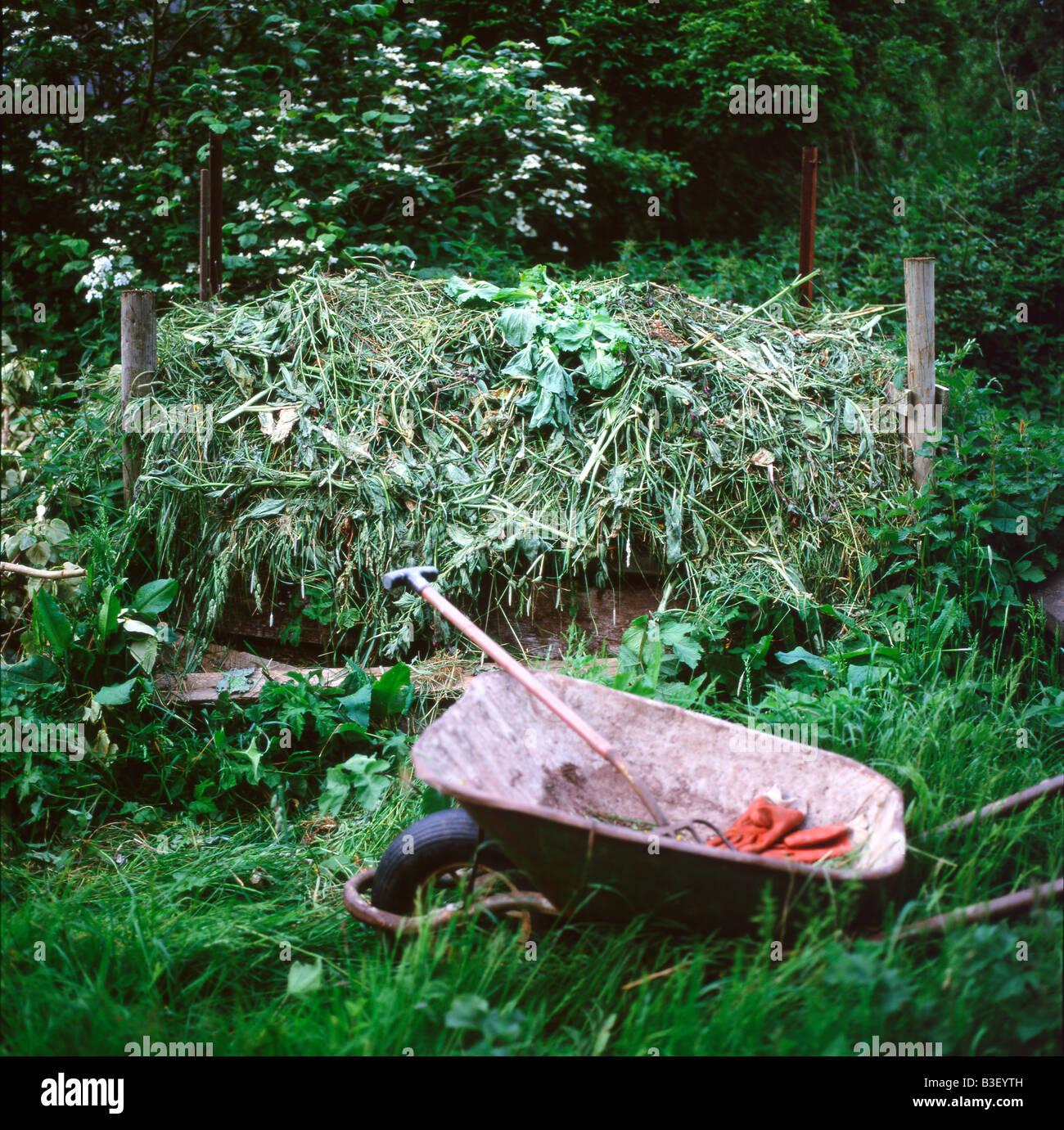 Compostera de cortes de césped, carretilla, horquilla y guantes de jardinería en un jardín autosuficiente Imagen De Stock
