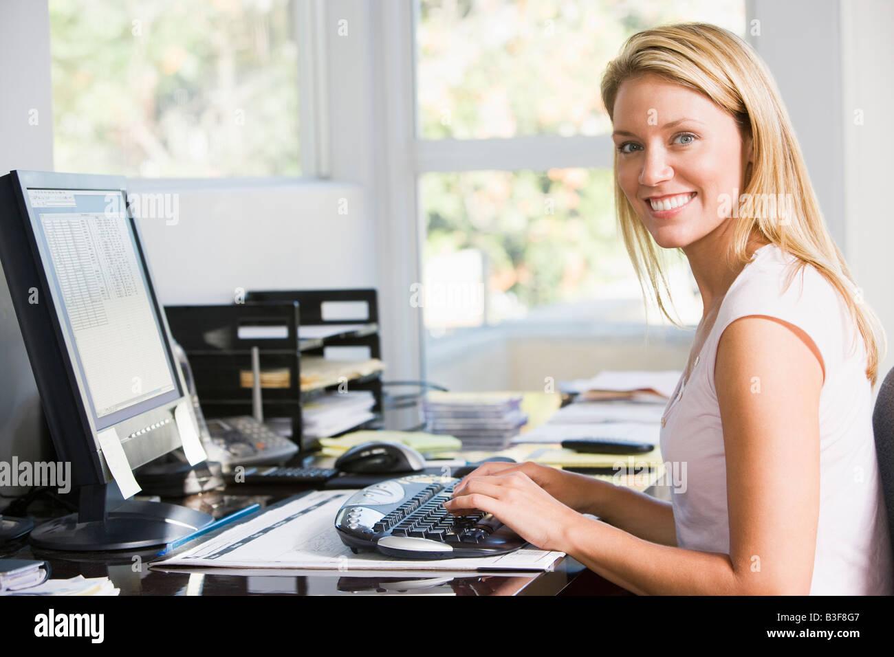 Mujer en su oficina doméstica con equipo sonriente Imagen De Stock