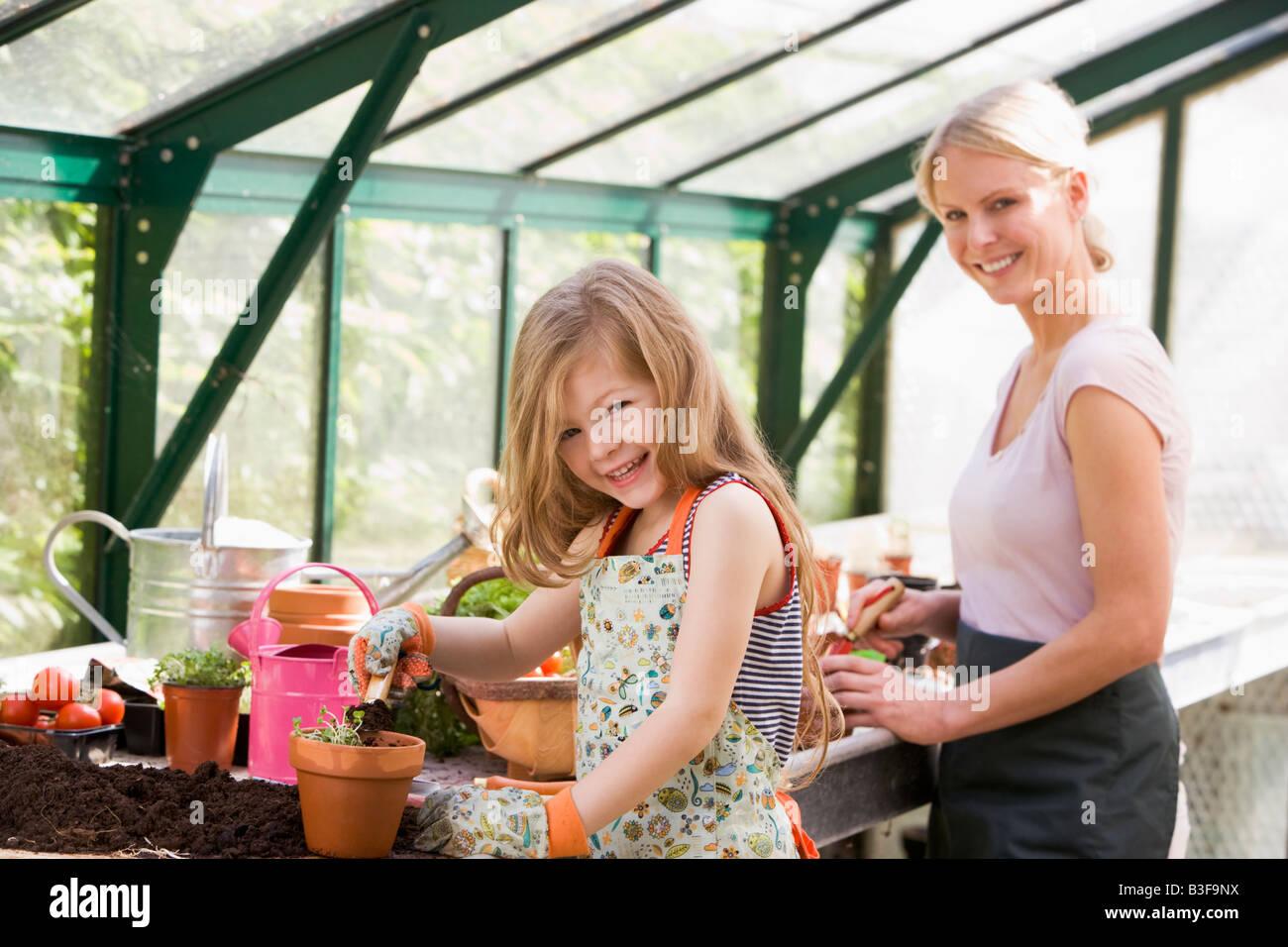 Niña y mujer en invernadero poner suelo en potes sonriendo Foto de stock