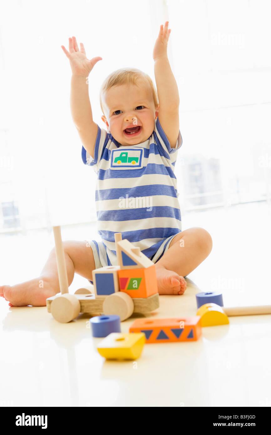 Bebé adentro jugando con carretilla Imagen De Stock