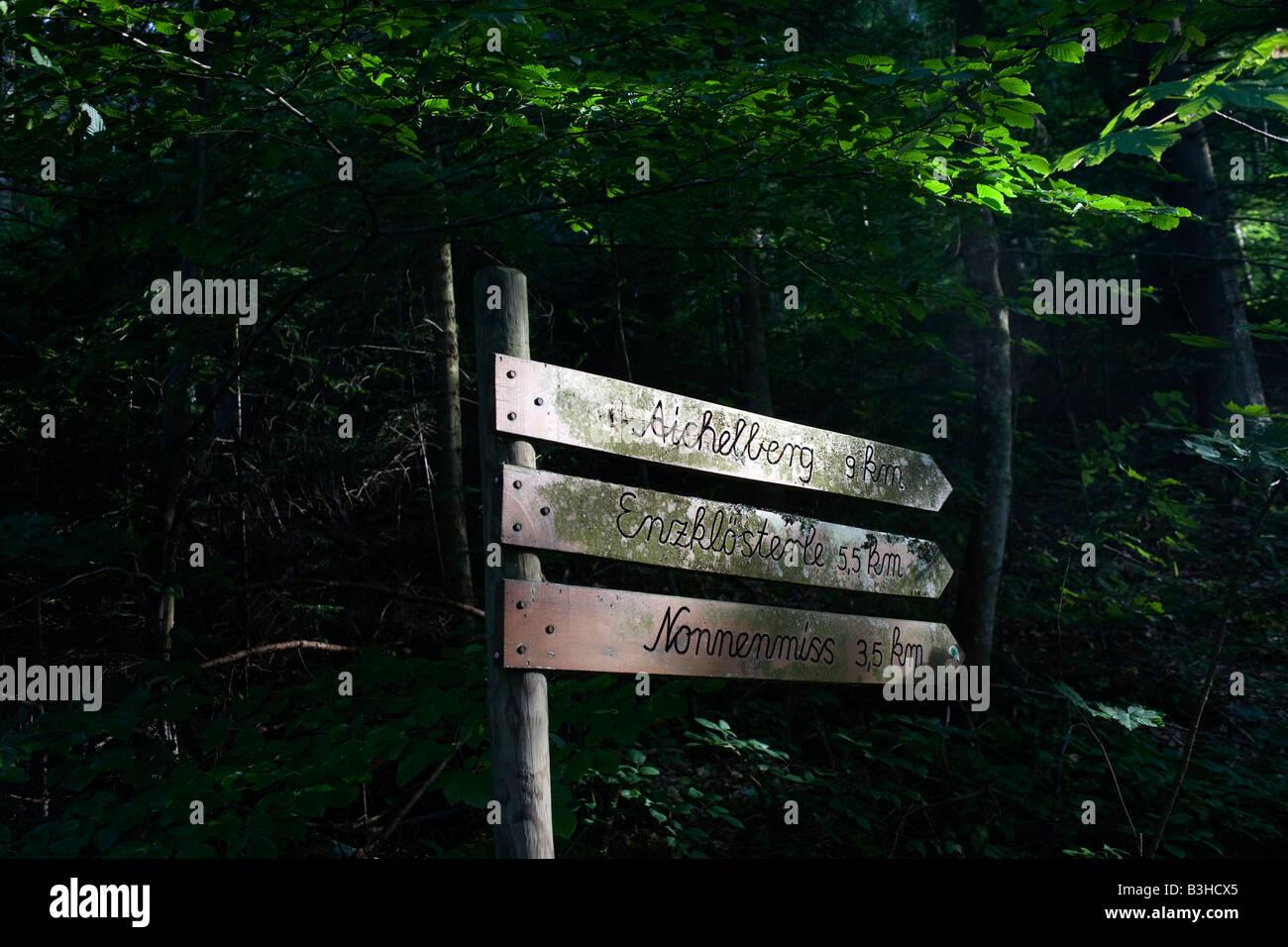 Ruta a pie signo marca distancia en km a través del bosque oscuro en la región de la Selva Negra alemana cerca de la aldea de Kälbermühle Foto de stock