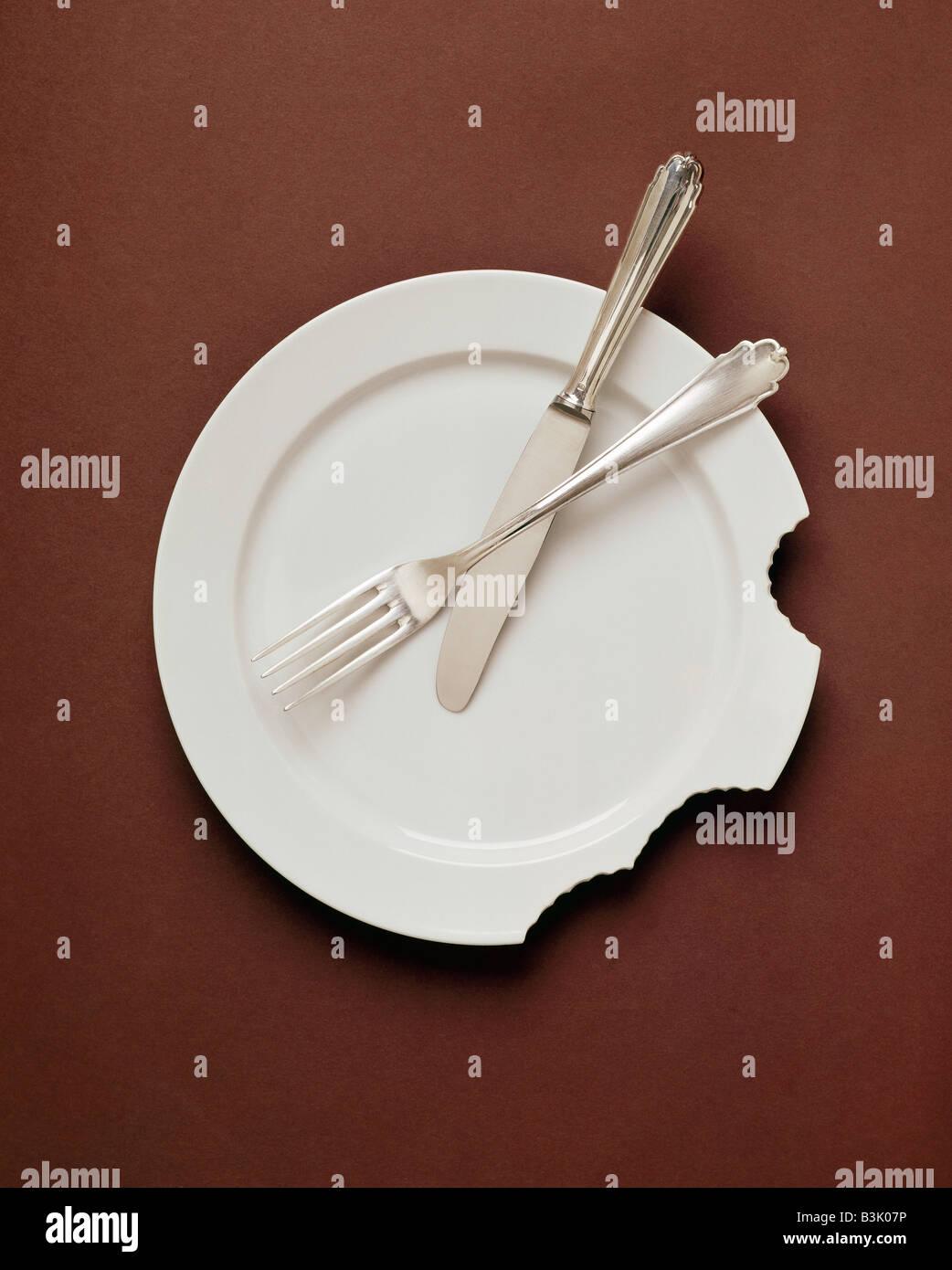 Tenedor y cuchillo en la placa blanca con MORDEDURAS HUMANAS Imagen De Stock