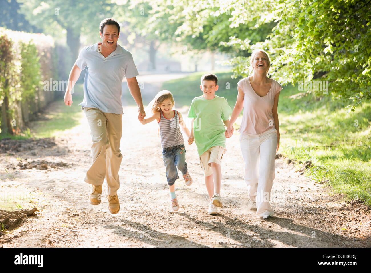 Ejecuta la familia afuera, tomados de la mano y sonriendo Imagen De Stock