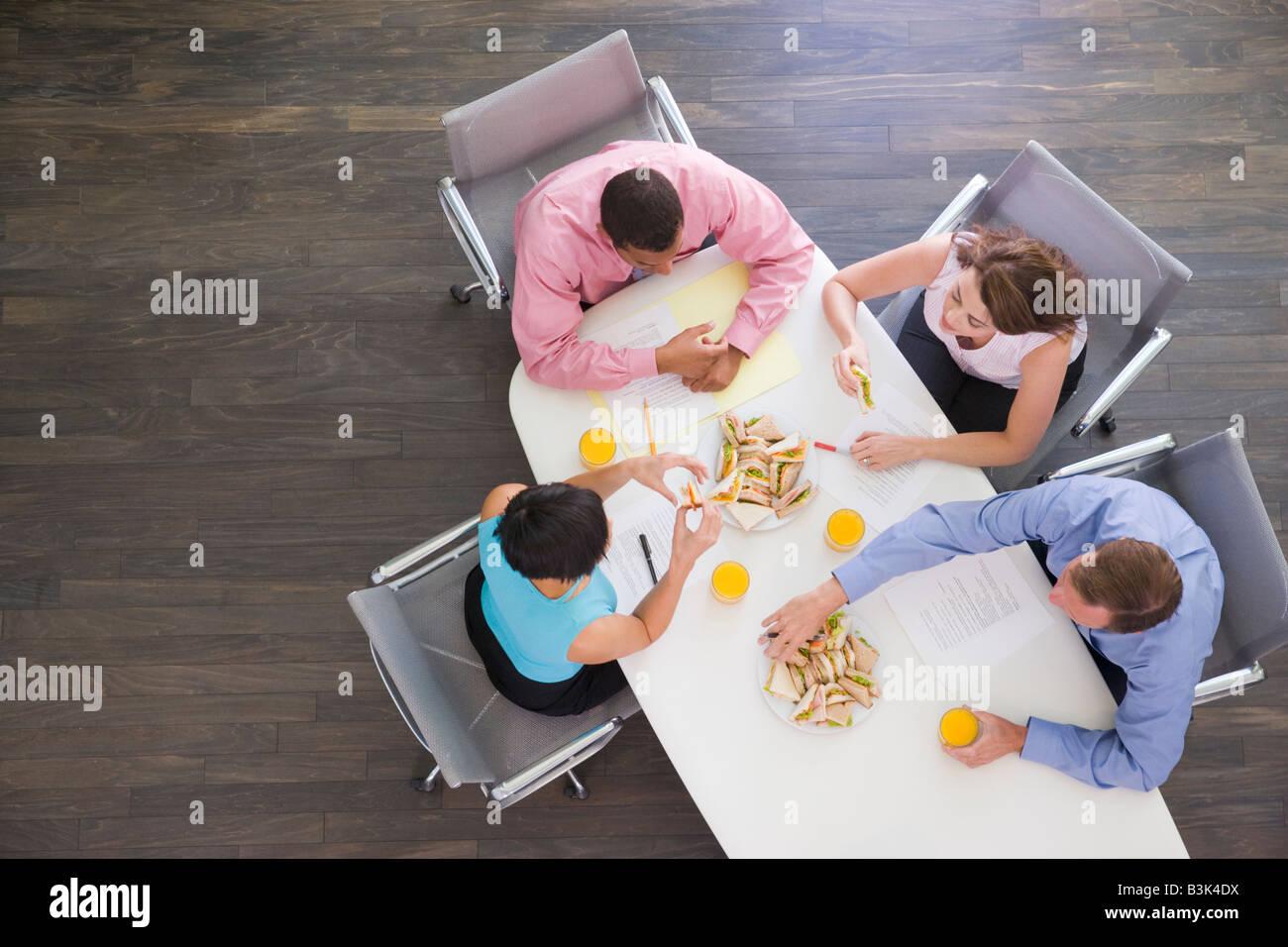 Cuatro empresarios en la mesa de juntas con sándwiches Imagen De Stock