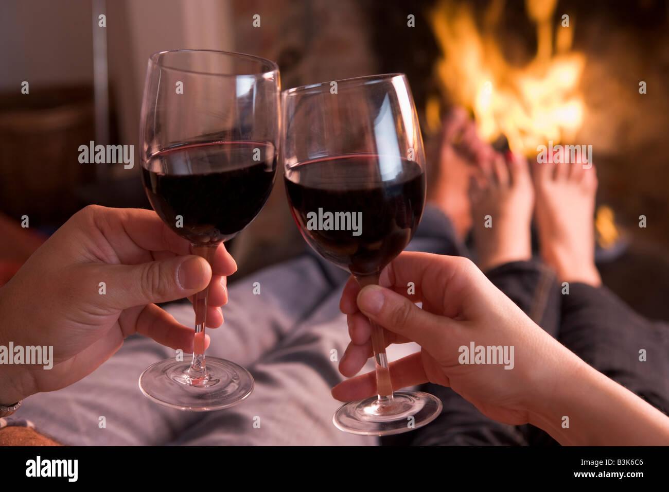 Pies calentando a chimenea con manos sosteniendo el vino Imagen De Stock