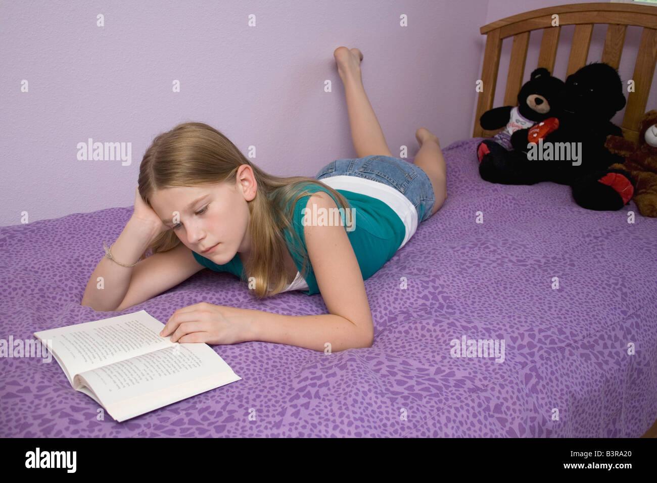 Niña Acostada En La Cama En Su Estómago Leyendo Un Libro