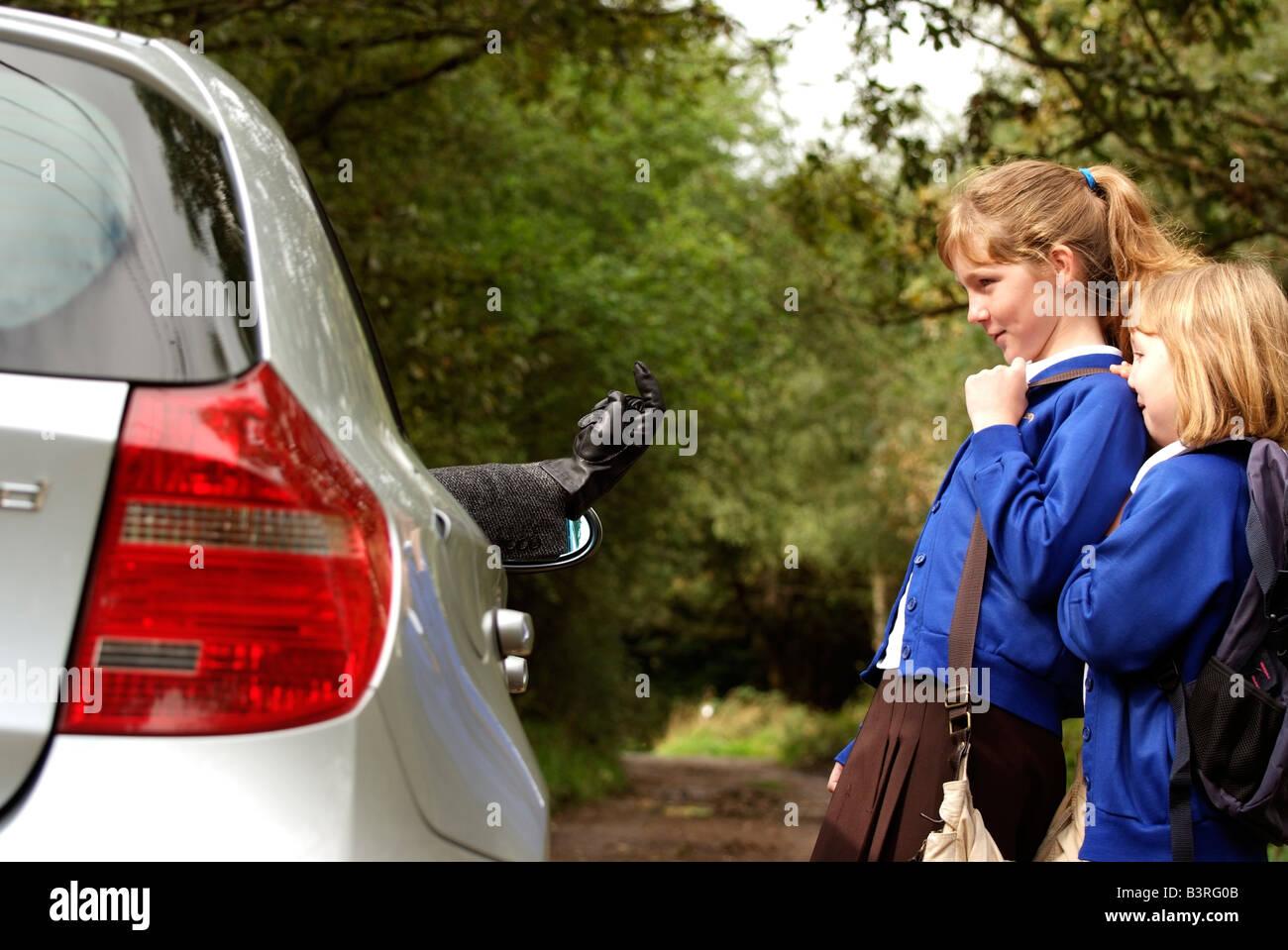 Motorista llevaba un guante de cuero negro atrae a las muchachas solas en un carril del país viajan a casa de la escuela Foto de stock