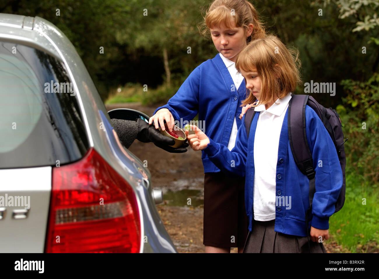 Las niñas solas en un carril del país tomar dulces de un extraño conduciendo un coche Foto de stock