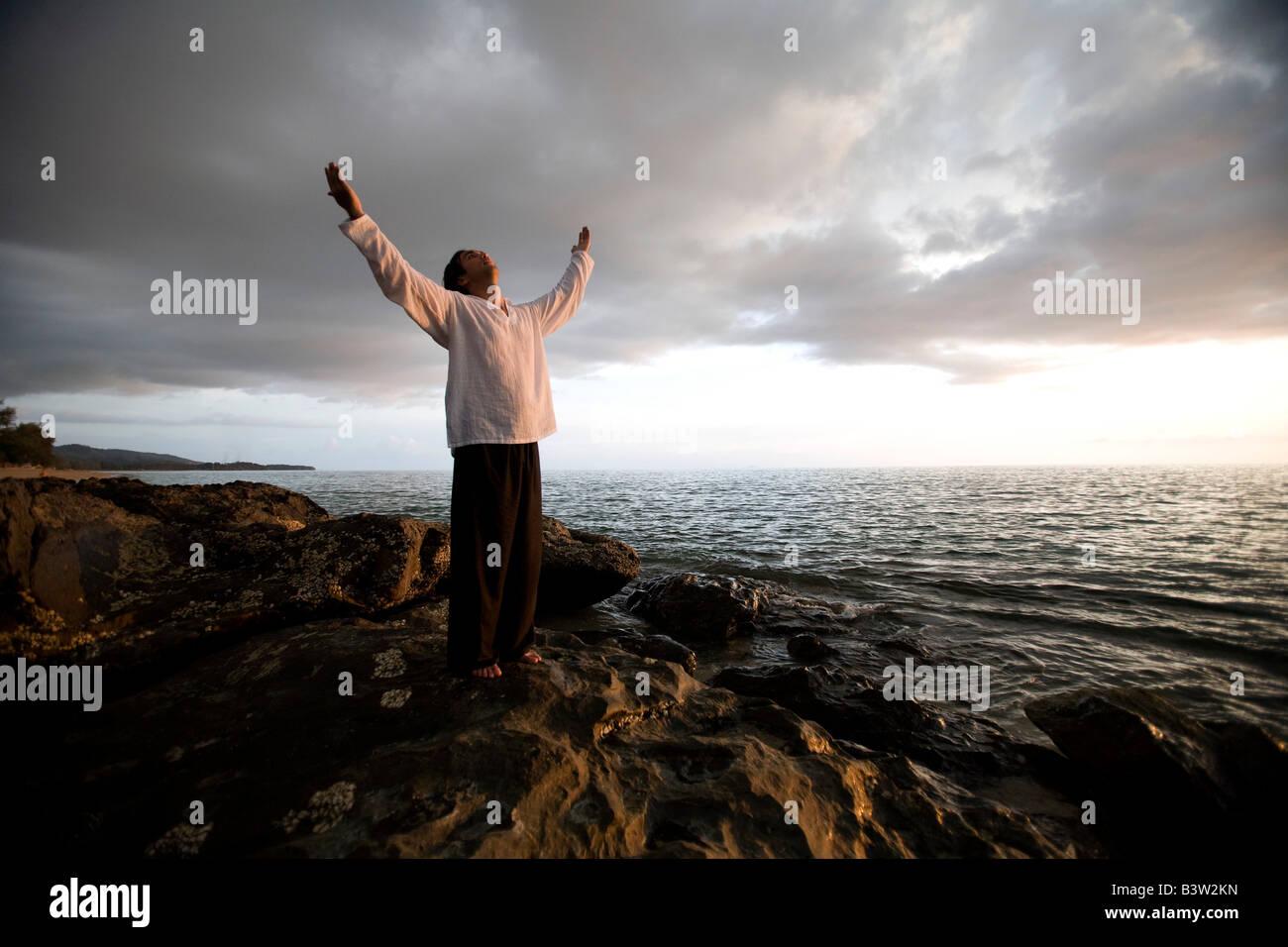 Una persona con los brazos levantados en una playa al atardecer, Koh Lanta, Tailandia, Asia Imagen De Stock