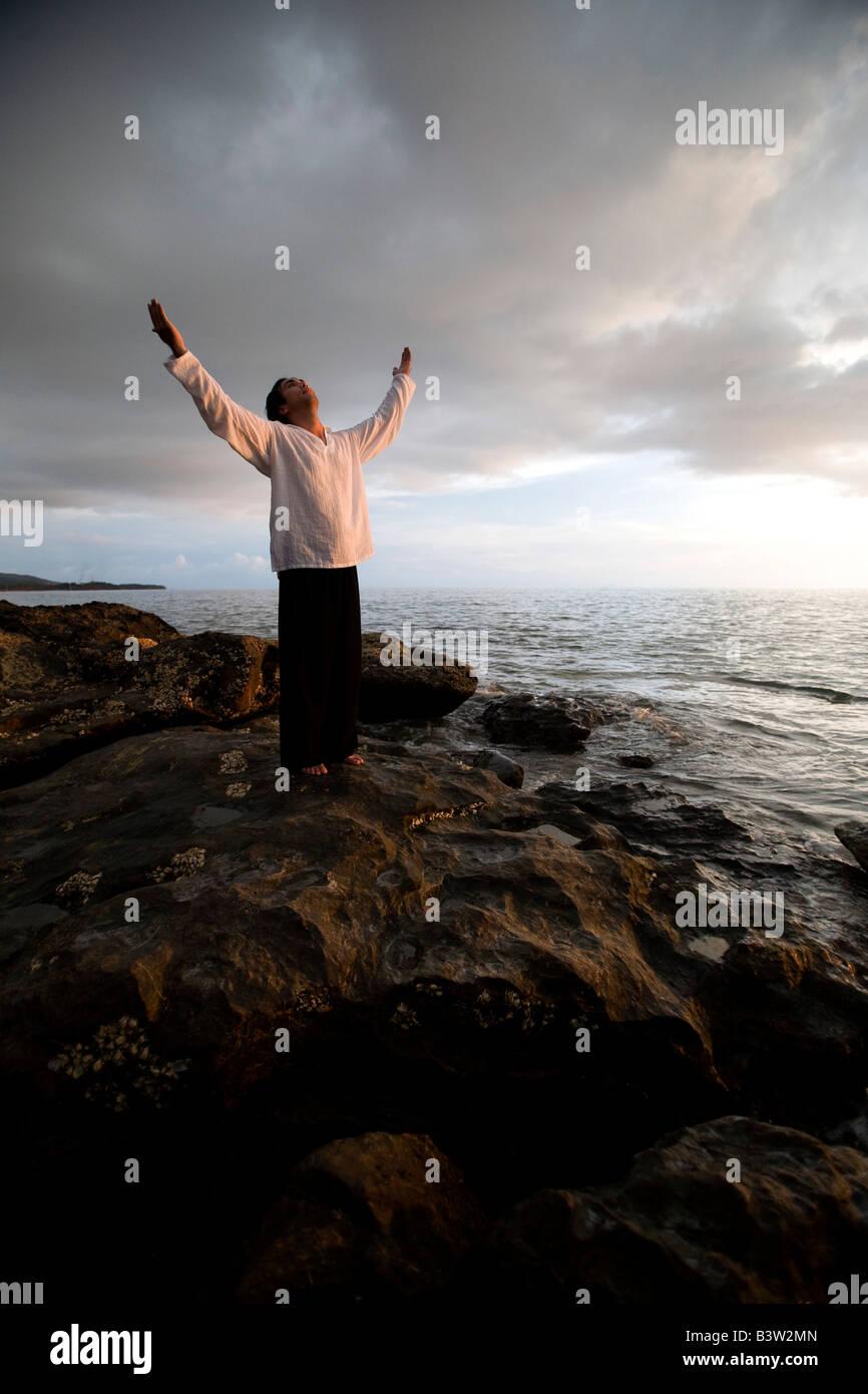 Una persona con los brazos levantados en una playa en el atardecer. Imagen De Stock