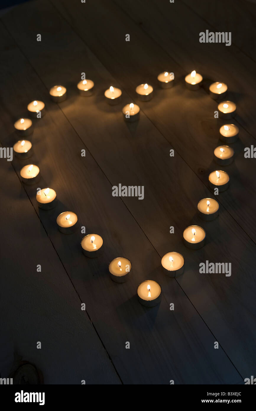 Encendido de velas colocadas en forma de corazón Imagen De Stock