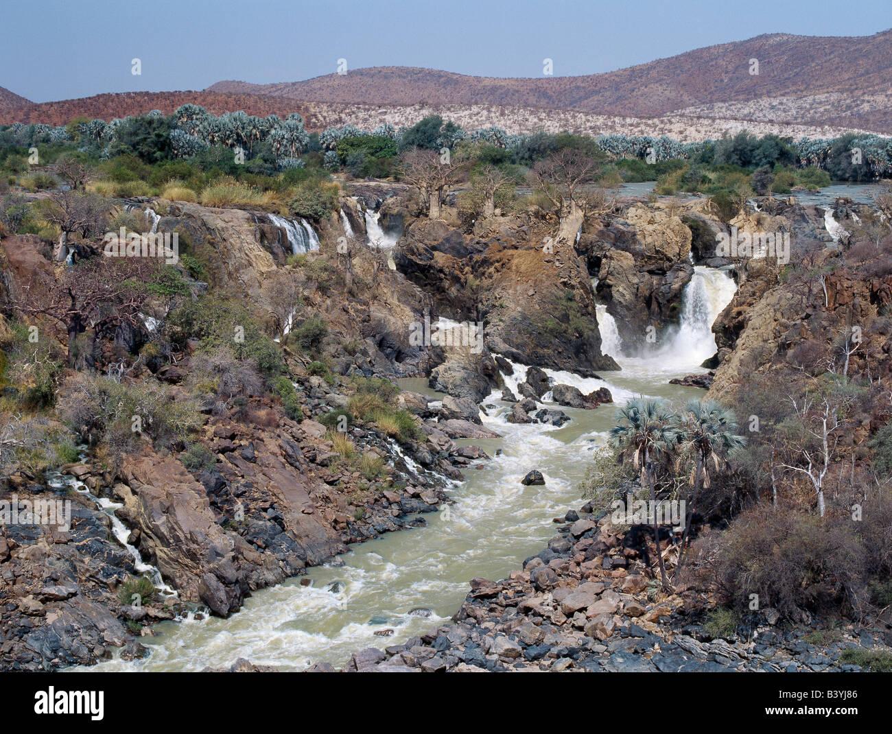 """Namibia, Kaokoland, Epupa. La atractiva Epupa Falls en el accidentado noroeste de Namibia son una serie de canales paralelos, donde el río Kunene desciende a 60 metros en un kilómetro y medio. En esta remota región, el río forma la frontera entre Angola y Namibia. """"Epupa' en el idioma Herero local significa 'Falling Waters'. Foto de stock"""
