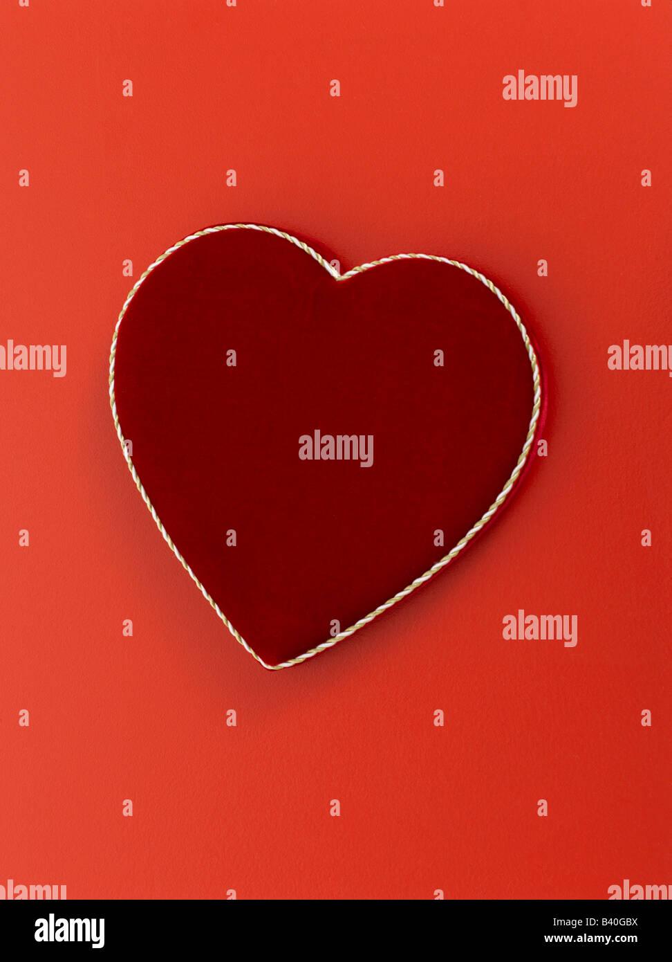 Día de San Valentín en forma de corazón caja de chocolates sobre fondo rojo. Imagen De Stock